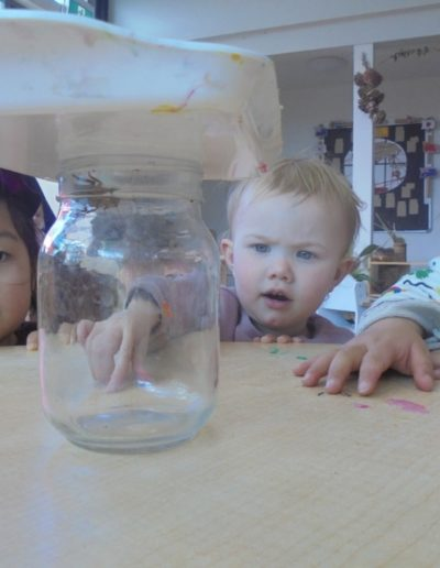 noelle isal and haru looking at a bug in a jar